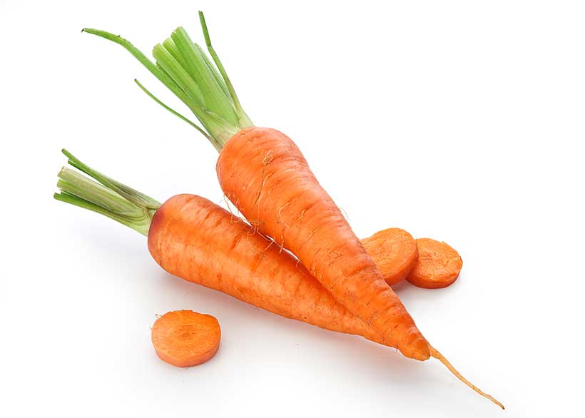 Picture of two carrots with some pieces of chopped carrot and green shoots.