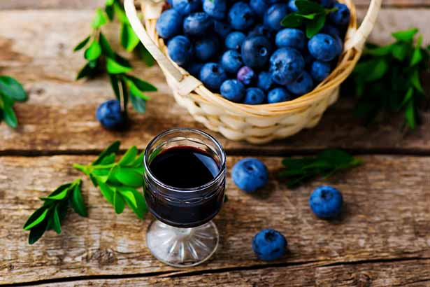 Picture showing blueberry wine and blueberries.