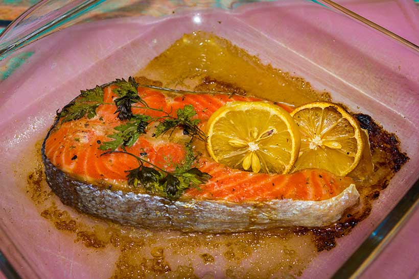 Picture of a baked salmon fillet covered with salt, pepper and a slice of lemon.