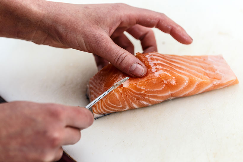 Picture of someone boning a fillet of salmon.
