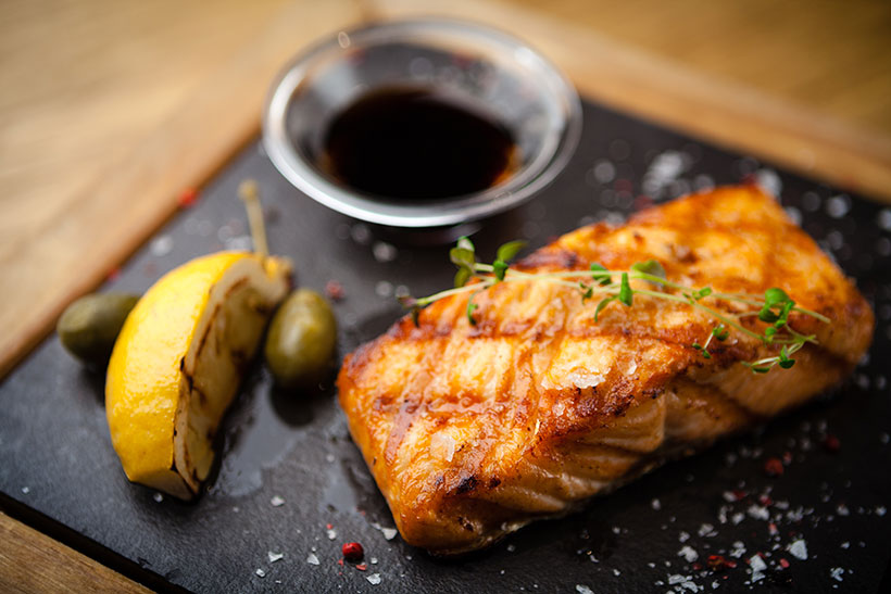Picture of grilled salmon with a slice of lemon and soy sauce.