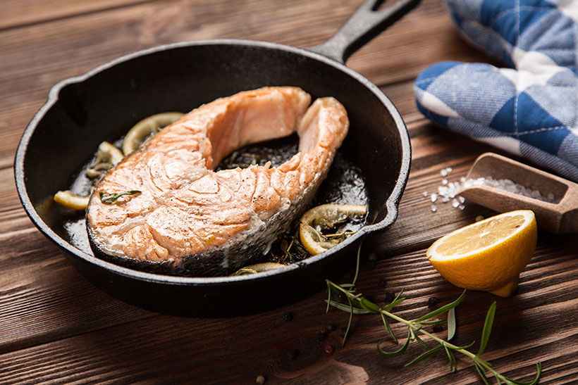 Picture of a pan-fried salmon fillet in a cast iron pan.