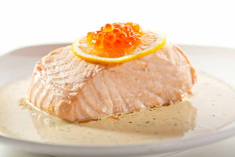 Picture of a poached salmon fillet in a creamy sauce.