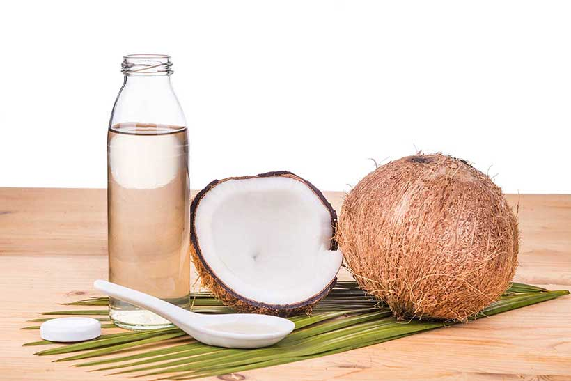 Picture of a coconut next to a bottle of fractionated coconut oil.