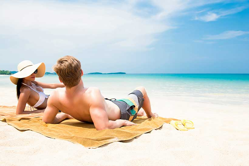 Picture of a Young Couple Sunbathing on the Beach.