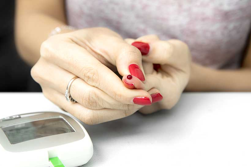 Picture of a Lady With Blood on Her Finger For Ketone Blood Meter.