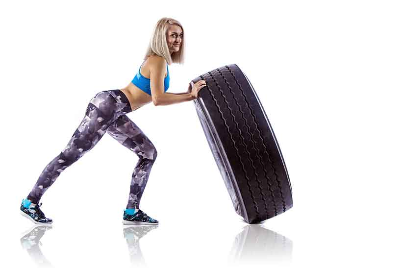 A Strong Young Woman Pushing Tires Over.