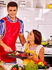 A Young Couple Cooking Beef On An Oven Tray.