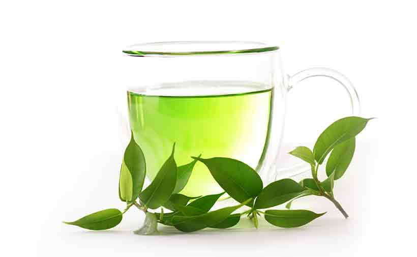 Picture of Green Tea With Leaves in a Glass Cup.