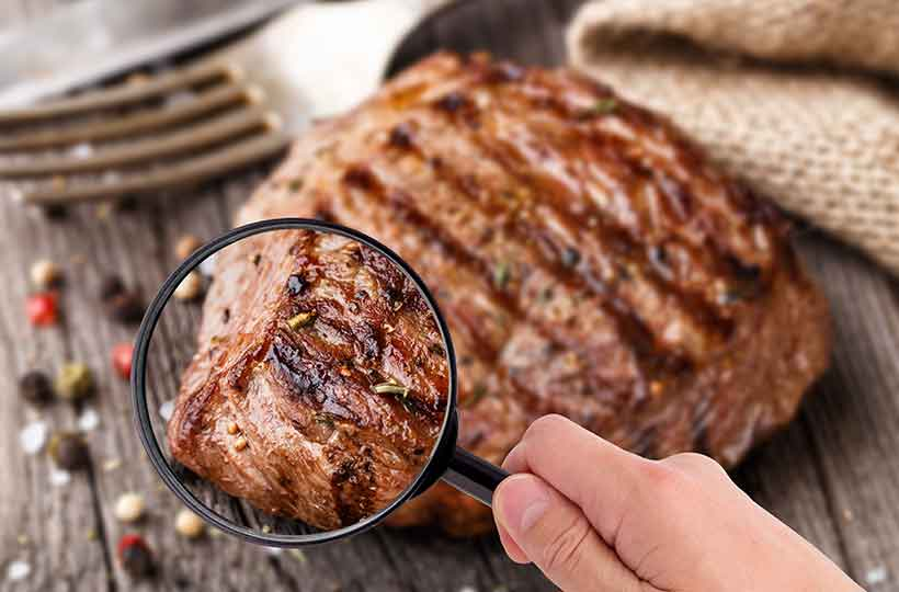 Someone Studying Red Meat With a Magnifying Glass.